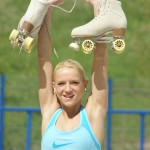 Sportlerin hebt Rollschuhe in die Höhe