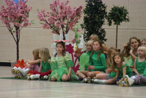 Kinder in Blumenkostümen sitzen auf dem Boden