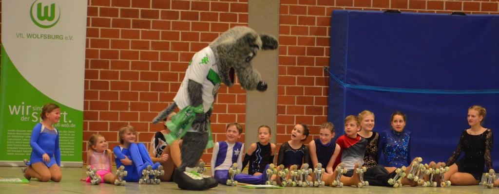 viele sitzende Sportler und ein stehendes Maskottchen im Wolfskostüm