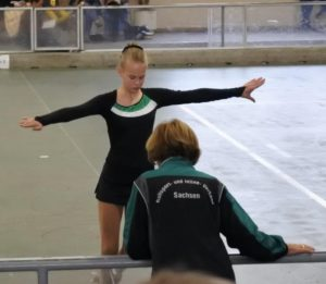 Rollkunstläuferin mit Trainerin