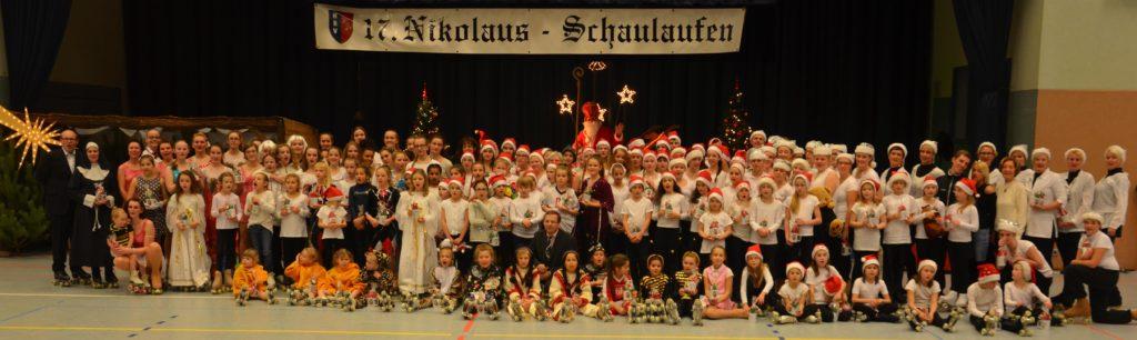 zirka 100 Personen mit aufgesetzter roter Mütze in weiß-schwarzen Kostümen