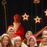Köpfe mit Nikolausmützen, dahinter ein Nikolaus