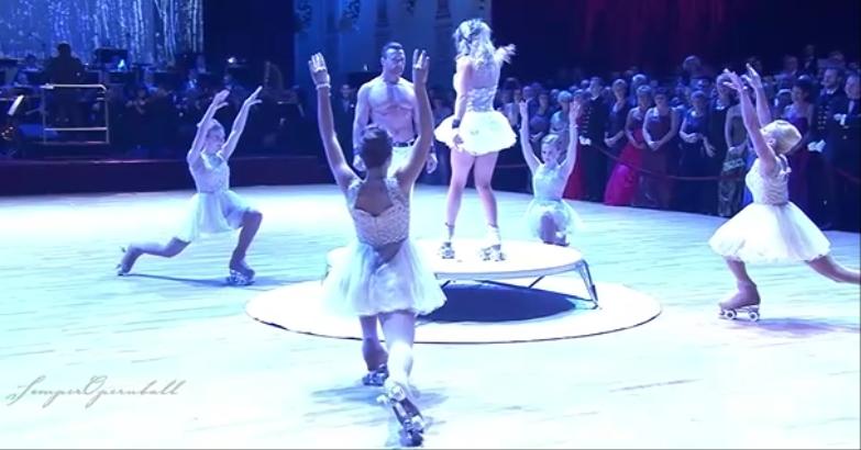 vier Rollkunstläuferinnen erheben die Arme zu zwei Künstlern auf einem Podest