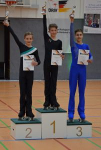 drei Jungen auf dem Podest heben ihre Pokale in die Luft