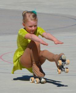 Rollkunstläuferin hält ein Bein in der Luft