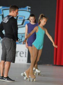 Rollkunstläufer mit Trainer